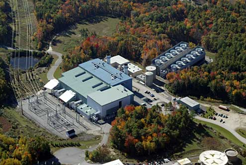 The green building houses the two gas turbines, the flat top section the steam turbine.  The cooling towers can be seen in the upper right.  The tank in the lower left is actually used for manufacturing yogurt at StonyField in Londonderry.