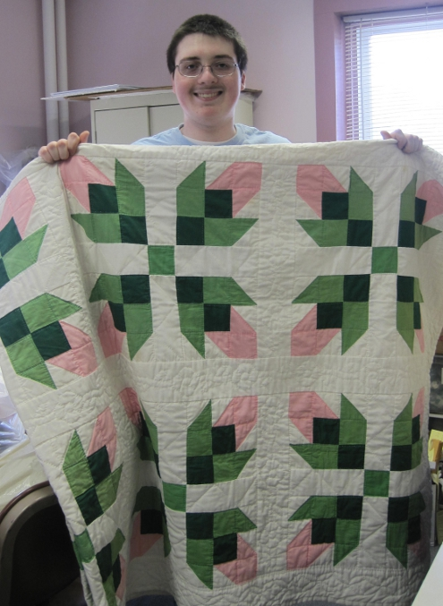 4-H member Chris St. Pierre of Lee displays a handmade quilt donated to this years 4-H Benefit Auction. This quilt and many more quality items and gift certificates will be up for auction on Saturday at the Stratham Fair.   